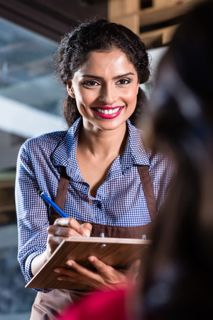 Waitress in indian restaurant or cafe taking orders, close