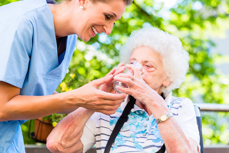 年配の女性に水のガラスを与える高齢者看護師