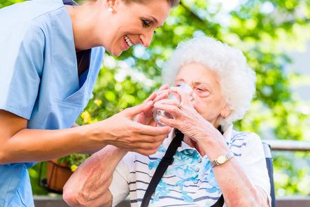 enfermera geriátrica dando vaso de agua a la mujer mayor