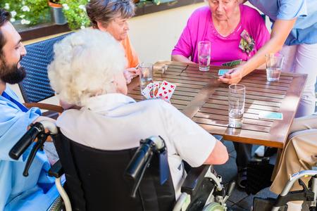 grupo de hombres: Grupo de personas mayores y las tarjetas de la enfermera que juegan en casa de reposo Foto de archivo