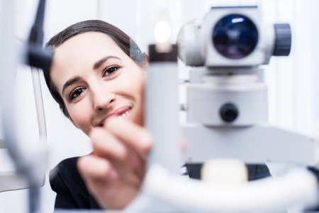 attempting: Optician attempting eye measuring with Refractometer Stock Photo