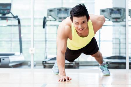 체육관에서 한 무장 한 팔 굽혀 펴기를 하 고 근육 질의 젊은 남자의 정면보기 스톡 콘텐츠