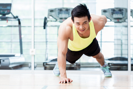 Frontale mening van gespierde jonge man doen eenarmige push-ups in de sportschool Stockfoto