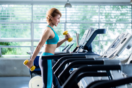 Shorthaired young woman doing exercises with dumbbells as additional weight while walking on treadmill in gym Фото со стока