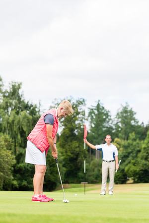 woman golf: Senior woman practicing with golf pro