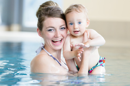 Mother and her newborn child at infant swimming class