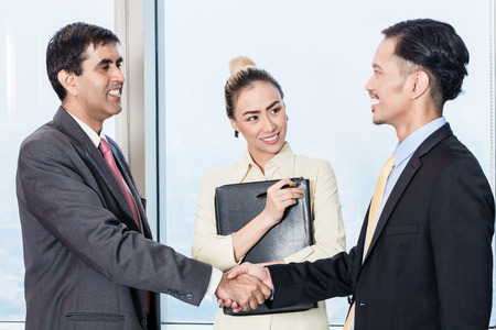 introduces: Asian secretary introduces applicant to boss for job interview and they shake hands in office Stock Photo