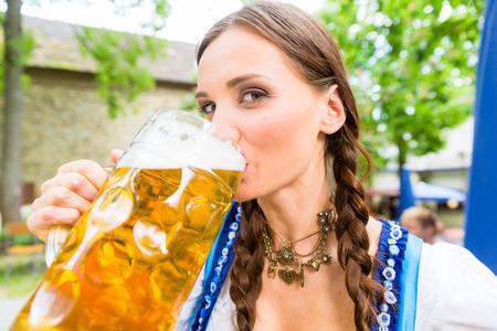 beer garden: Woman wearing Dirndl is drinking beer in a Bavarian beer garden