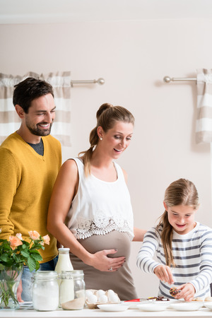 quality home: Family with pregnant mother, father and daughter baking together in kitchen Stock Photo