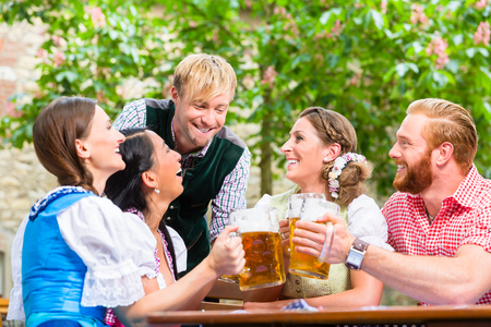 ive friends in Bavarian clothes clinking beer glasses in beer garden Stock Photo