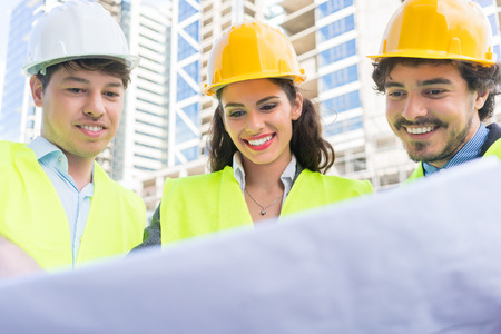 statics: Architects and civil engineers with ground plot on construction site of highrise building Stock Photo