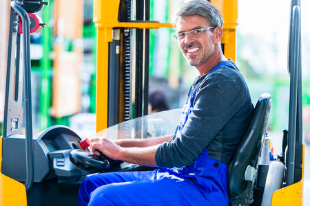 Home improvement store clerk driving forklift in warehouse for DIY equipment