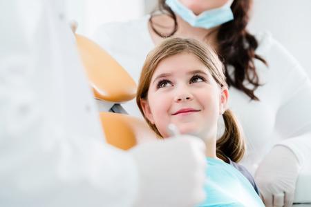 Tandarts trearing kind in zijn chirurgie, is er geen noodzaak om een tand te boren Stockfoto