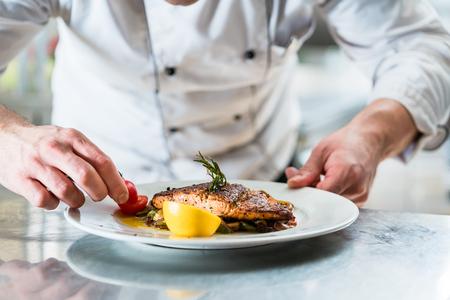 Chef-kok met ijver afwerking schotel op de plaat, vis met groenten