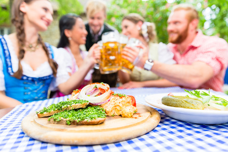 obazda: Five friends, women and men, sitting in beer garden clinking glasses having Bavarian appetizers on the table Stock Photo
