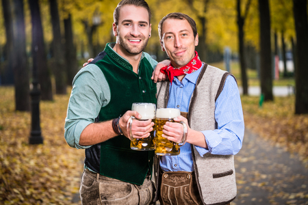 bier: Two men in Bavarian Tracht, clinking glasses with a Mass Bier Stock Photo