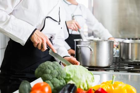 Personas de los cocineros que preparan el alimento en la cocina industrial Foto de archivo - 64981785