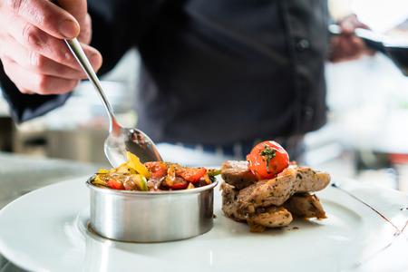 comida: Chef de terminar la comida en el plato en el hotel o restaurante cocina Foto de archivo