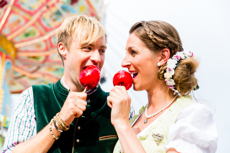Woman and man biting red candy apples wearing Bavarian traditional clothes in front of carousel