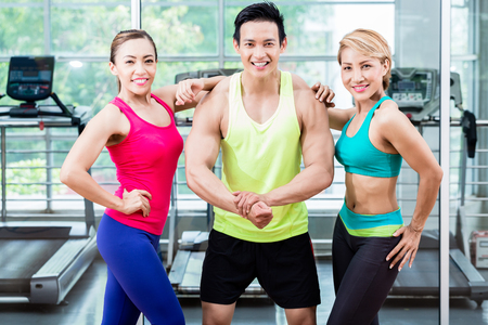 strong woman: Muscular young man amongst two sportive women striking a pose and presenting his muscles