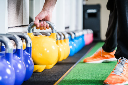 Man lifting kettlebell from floor doing sport in gym