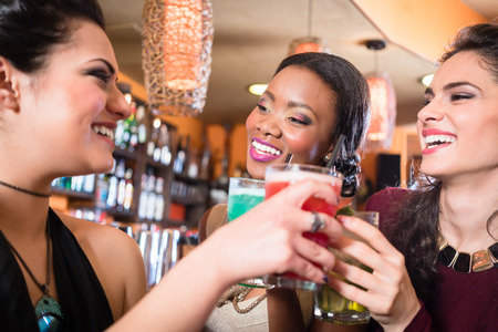 night out: Beautiful girls in nightlife drinking cocktails and saying Cheers