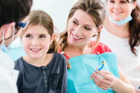 Dentist and his assistant with pregnant woman and child in surgery Banco de Imagens - 64981808