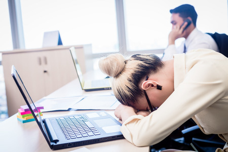 Young Asian business woman taking nap in office being exhausted and overworked Stock Photo