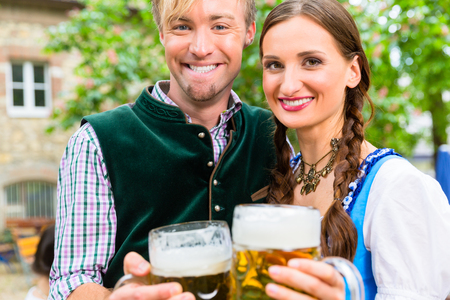 beer garden: Couple, women and man, wearing Bavarian clothes is clinking beer glasses in a beer garden