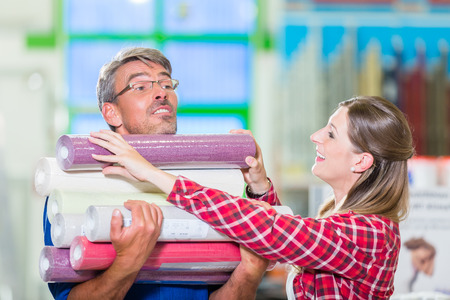 doityourself: Home improving couple, woman and man, buying many rolls of wallpapers at hardware store for do-it-yourself project Stock Photo