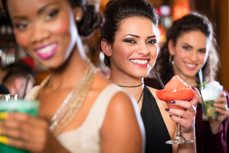 Grupo multicultural de las mujeres después de beber cócteles en el trabajo de barras Foto de archivo - 63375245