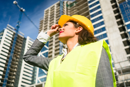 female architect: Female architect visiting construction site of high-riser Stock Photo