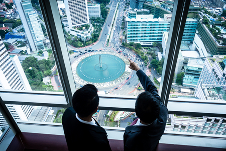 business development: Two Asian business people looking down to city streets from skyscraper office building discussing real estate development Stock Photo