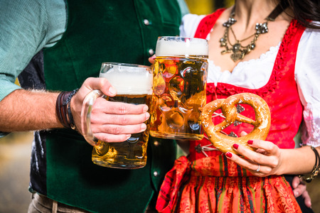 tradition: Hands holding Beer and Pretzels, detail of bavarian Tracht Stock Photo
