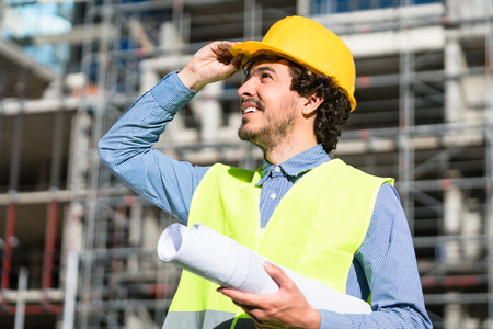 housing lot: Construction engineer studying floor plan in front of building shell at construction site