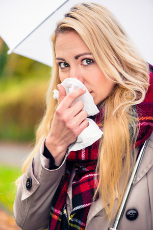 hanky: Woman having cold or flu due to bad autumn weather