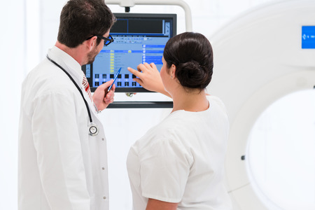 tomograph: Doctor and nurse analyzing data of CT scan on screen in hospital Stock Photo