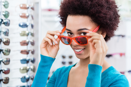 optician: Black woman wearing and buying sunglasses in optician shop
