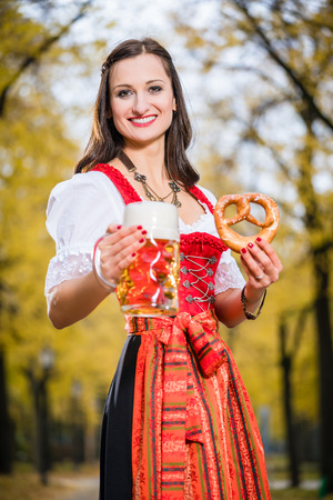 people laughing: Woman in traditional Dirndl, carrying a beer mug and a Pretzel, standing Stock Photo