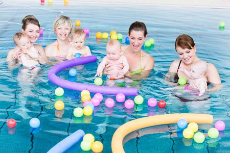 Moeders en hun baby's samen spelen met ballen en zwembad noedels bij baby zwemles