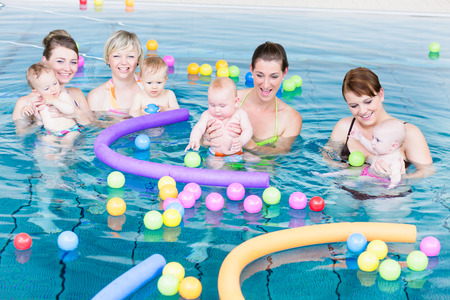Moms and their newborns playing together with balls and pool noodles at infant swimming class Imagens
