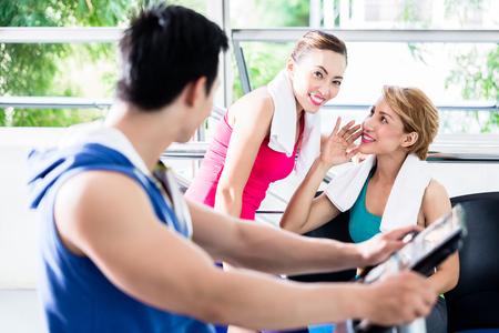 hombre deportista: Deportista joven en la rueda de ardilla gira la cabeza hacia la sonrisa de las niñas que lo observaban durante el entrenamiento Foto de archivo