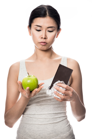 debating: Pretty Asian woman debating an apple or chocolate as she stands with a fresh green apple in one hand and unwrapped bar of candy in the other in a healthy diet concept