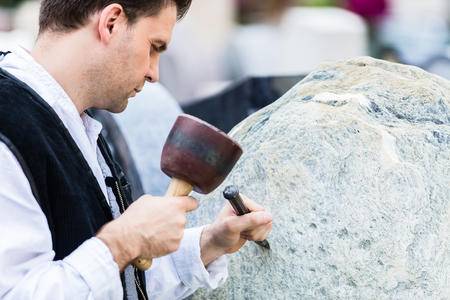 erratic: Sculptor with mallet and cutter working on erratic block Stock Photo