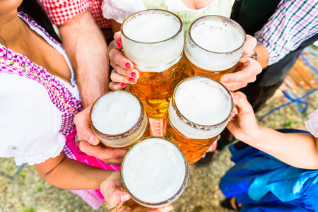 Clinking glasses with beer in Bavarian beer garden, close-up on five beer glasses Stock Photo