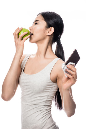 Attractive Asian woman opting for a healthy diet turning to bite into a fresh green apple while holding an unwrapped bar of chocolate aside