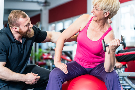 senior woman: senior woman working out with dumbbells with personal trainer