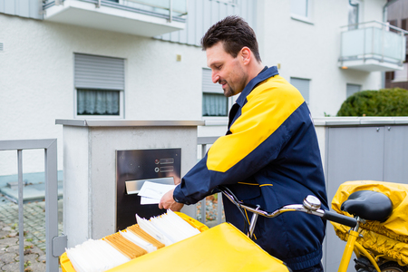 Postman delivering letters to mailbox of recipient 写真素材