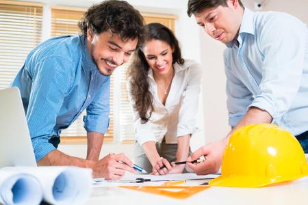 trabajando duro: ingenieros civiles y arquitectos que hablan de parcela de tierra para la construcción