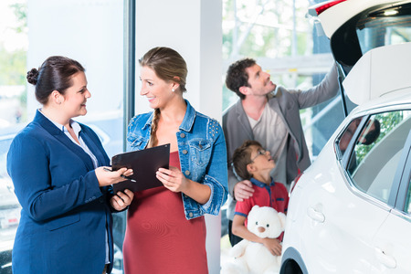 used: Family buying new car in auto dealer showroom, the sales lady shows the price list